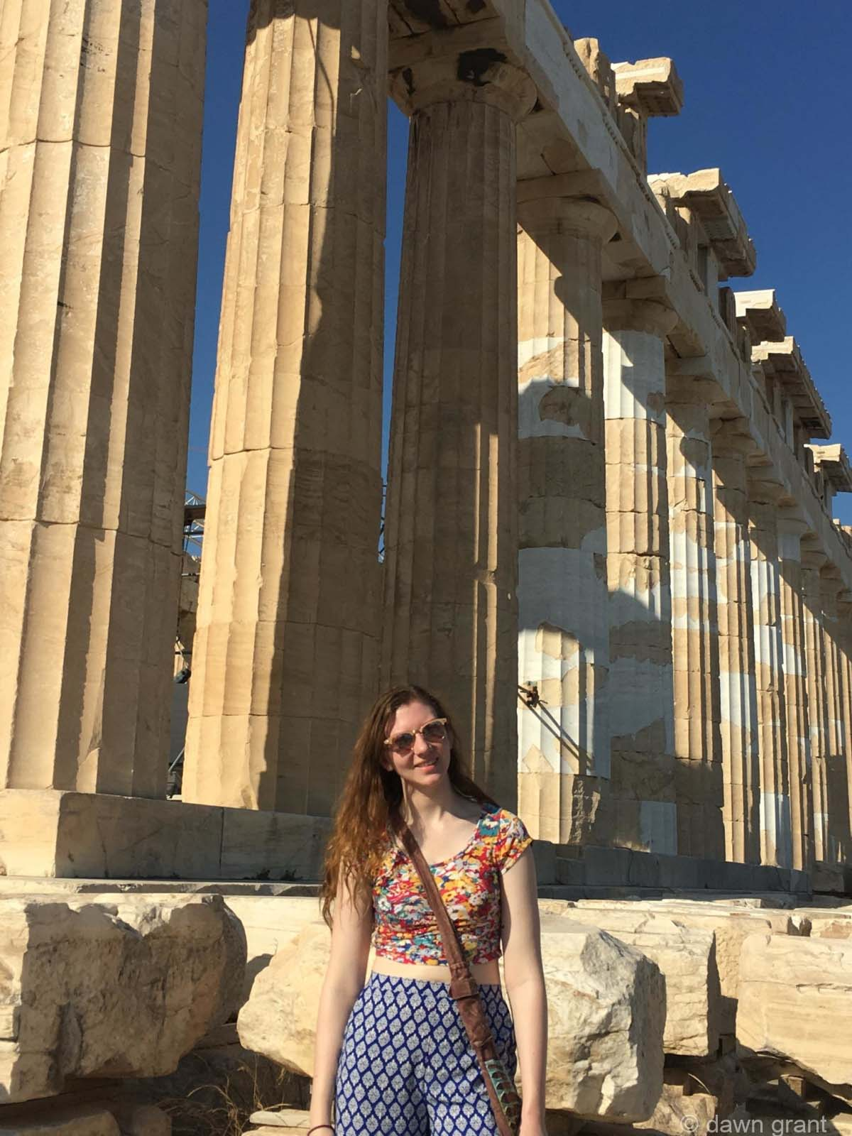 A young woman stands in front of the Parthenon ruins showing large columns that are obviously very old.