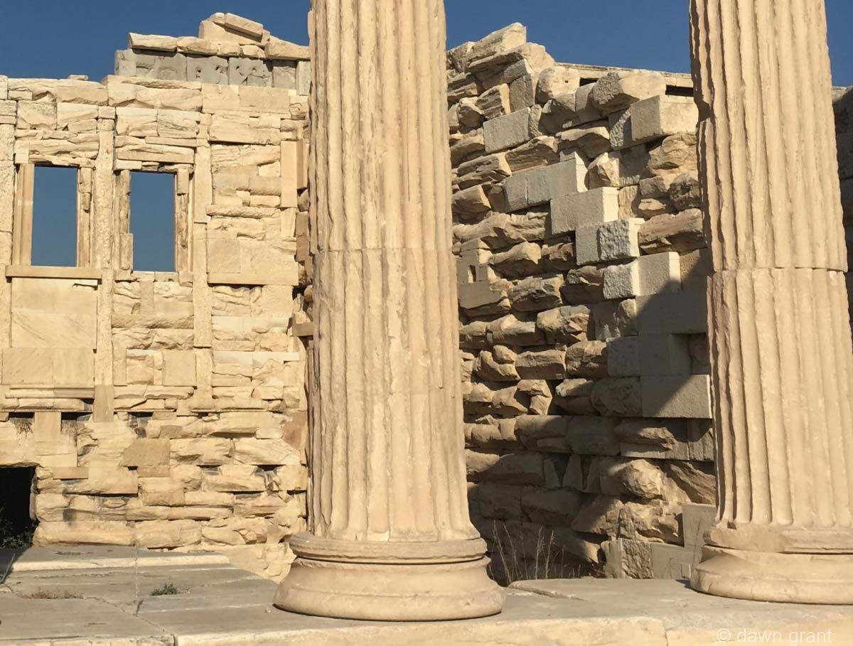 A closer view of columns that are very aged with brickwork behind where you can see centuries of erosion.