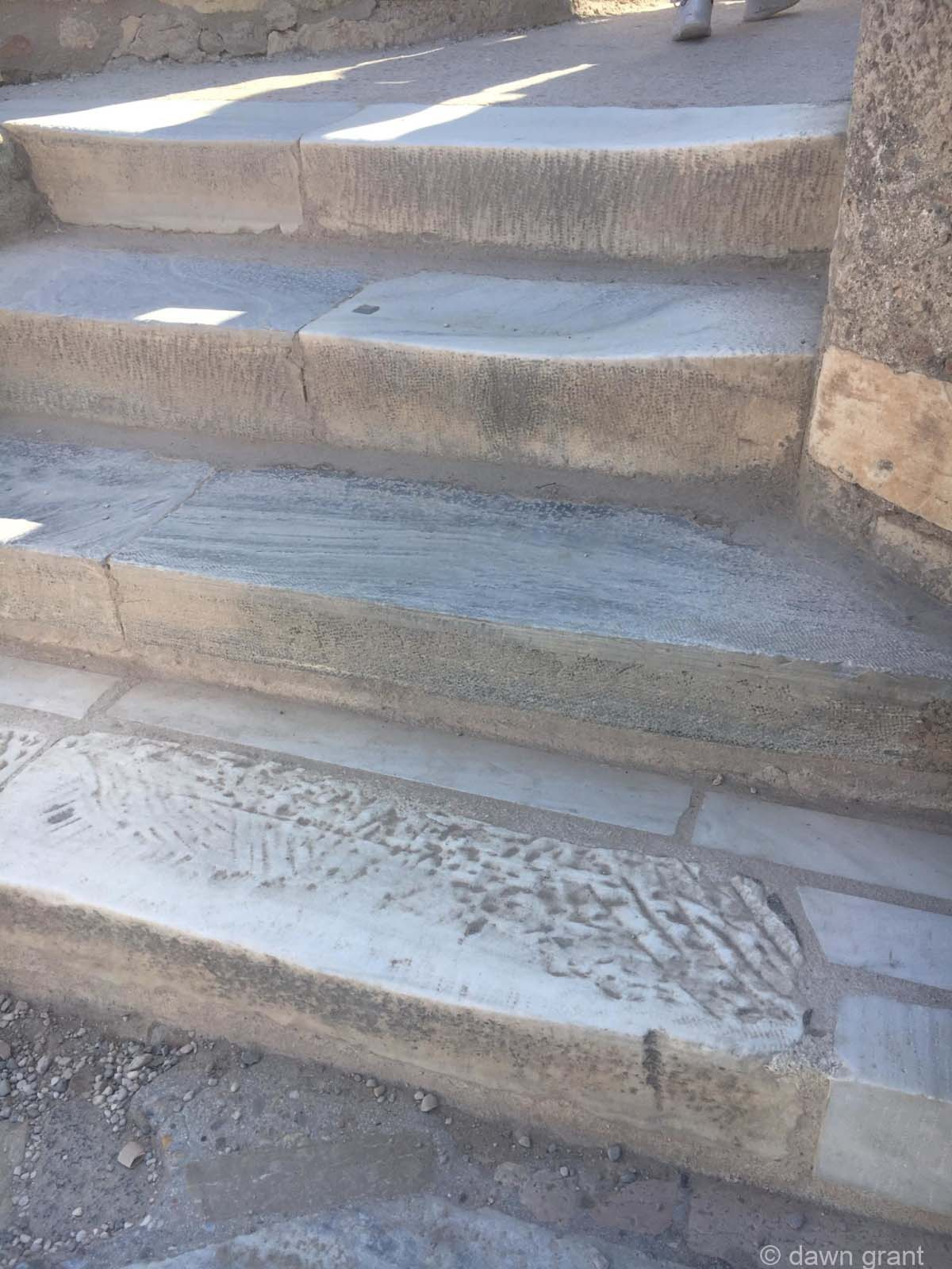 A close look at stone stairs that have been worn down by feet climbing them over centuries.
