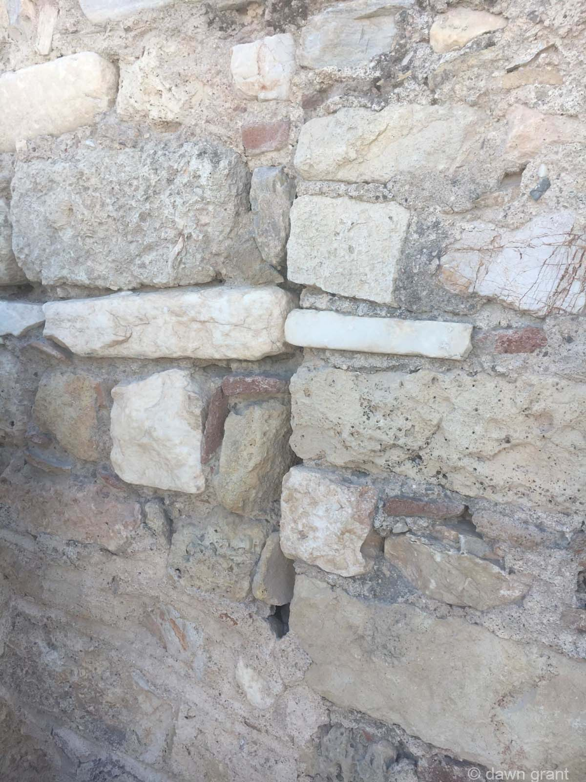 A close up of an old wall made of several different bricks and plaster.