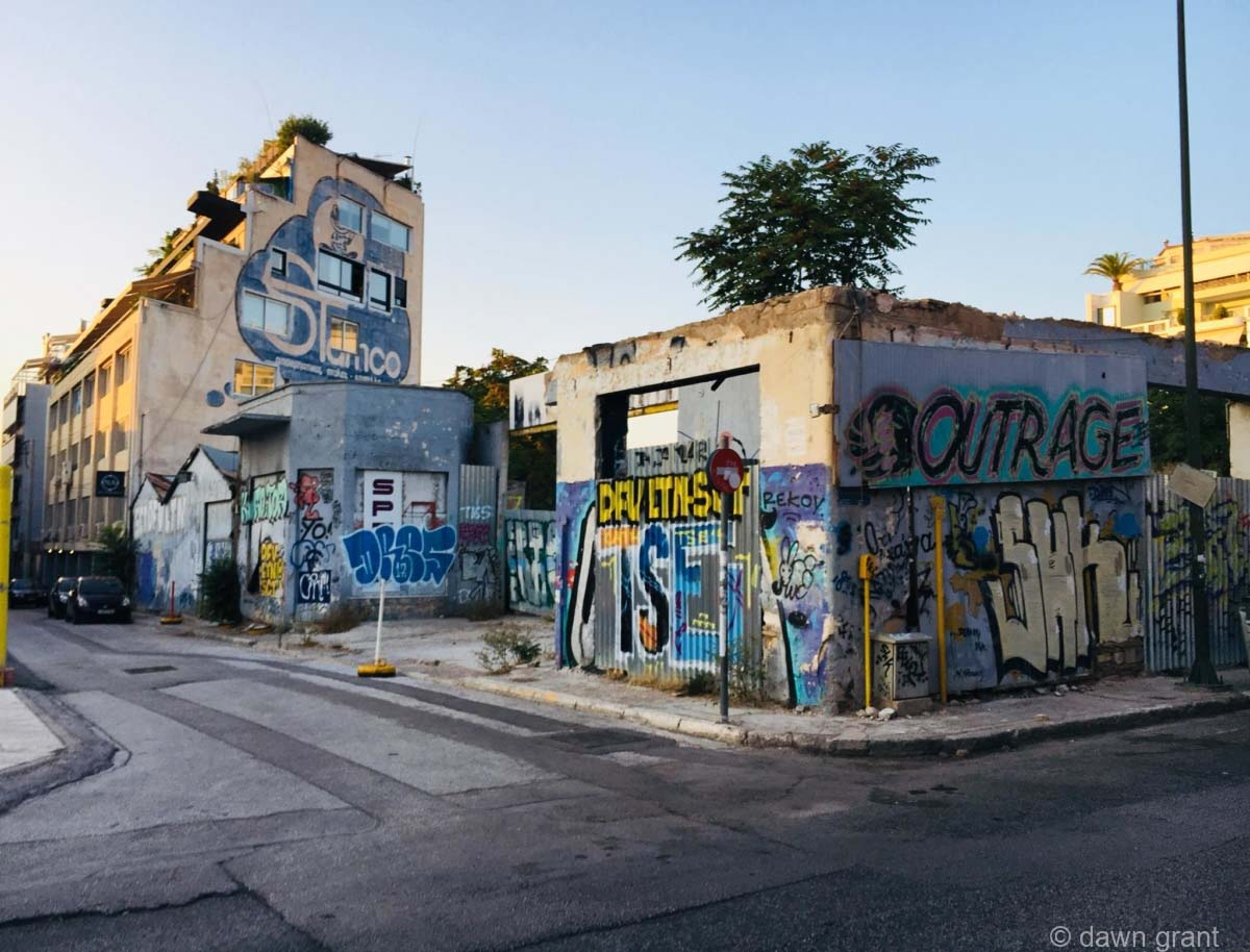 A newer stucco-type building completely covered in mostly-blue graffiti in English and Greek.