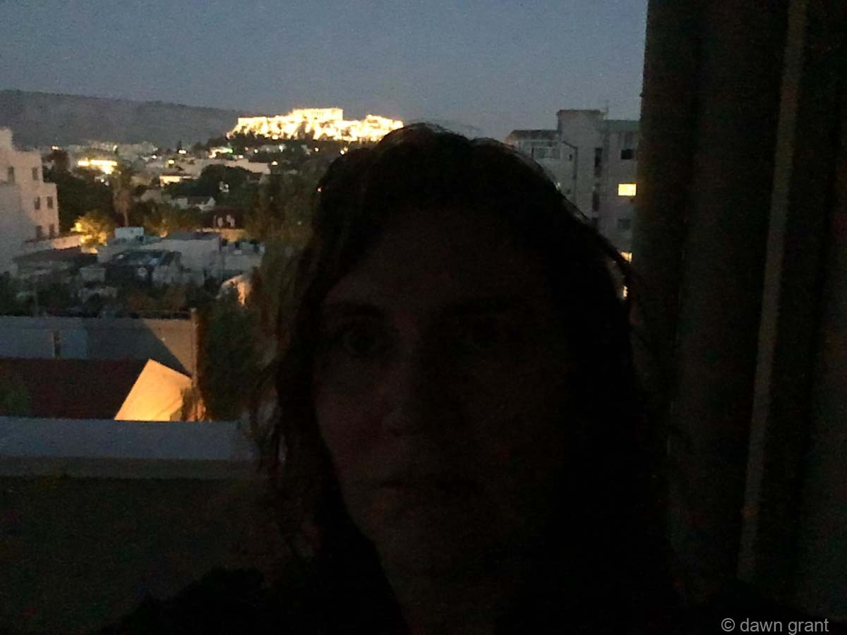 A photo taken at night with person in the foreground, city lights behind, and the Acropolis lit up on the hill.